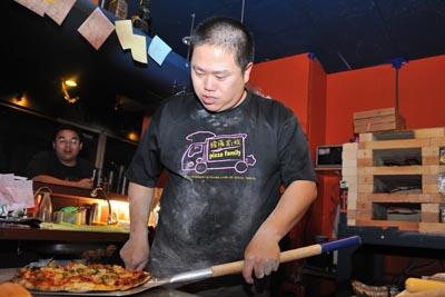 原為披薩車移動販售的手工窯烤Pizza,現已落腳新莊區中華路轉為實體店面經營,Pizza的製作過程仍保留窯烤的特色。記者王騰毅攝影。